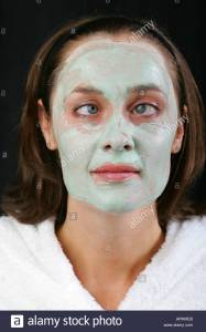 young-woman-with-green-avocado-face-pack-smiles-and-crosses-her-big-apmheb
